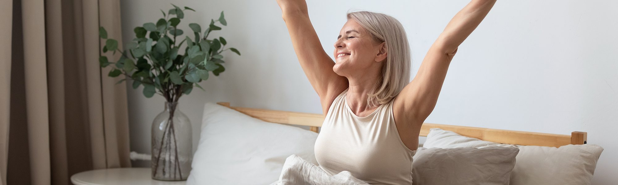 Happy mature woman stretching in bed waking up happy concept